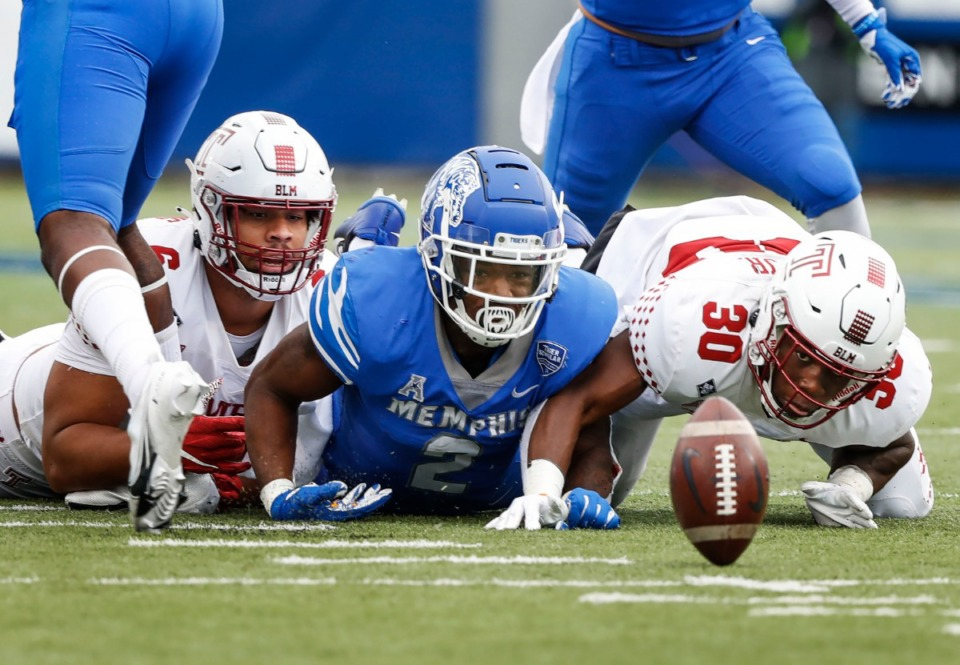 <strong>Memphis running back Rodrigues Clark (middle) watches a fumbled ball bounce away while flanked by Temple defenders Daniel Archibong (left) and Audley Isaacs (right) during action on Saturday, Oct. 24, 2020 at Liberty Bowl Memorial Stadium. Temple recovered the ball on the play.</strong> (Mark Weber/The Daily Memphian)