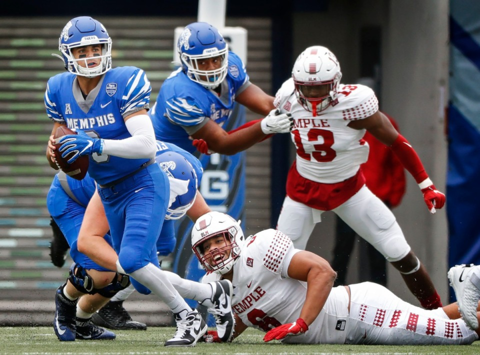 <strong>Memphis quarterback Brady White (left) scrabbles out of the grasp of Temple defender Daniel Archibong (bottom right) during action on Saturday, Oct. 24, 2020 at Liberty Bowl Memorial Stadium.</strong> (Mark Weber/The Daily Memphian)