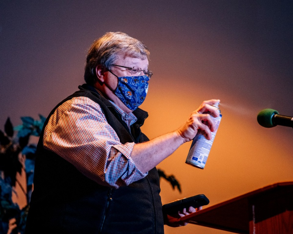 <strong>Memphis Mayor Jim Strickland sprays disenfectant on a microphone before speaking Saturday, Oct. 24, 2020 at Limit Breaker Church.&nbsp;</strong>(Houston Cofield/Special To The Daily Memphian)