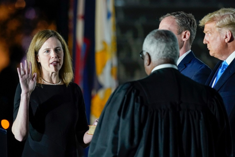 <strong>President Donald Trump watches as Supreme Court Justice Clarence Thomas administers the Constitutional Oath to Amy Coney Barrett on the South Lawn of the White House in Washington, Monday, Oct. 26, 2020, after Barrett was confirmed to be a Supreme Court justice by the Senate earlier in the evening. Holding the Bible is Barrett&rsquo;s husband, Jesse Barrett.</strong> (AP Photo/Patrick Semansky)