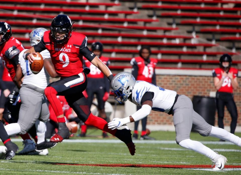 <strong>Cincinnati quarterback Desmond Ridder (9) scrambles away from Memphis defensive back Rodney Owens, right, during the first half of an NCAA college football game Saturday, Oct. 31, 2020, in Cincinnati.</strong> (Gary Landers/AP)