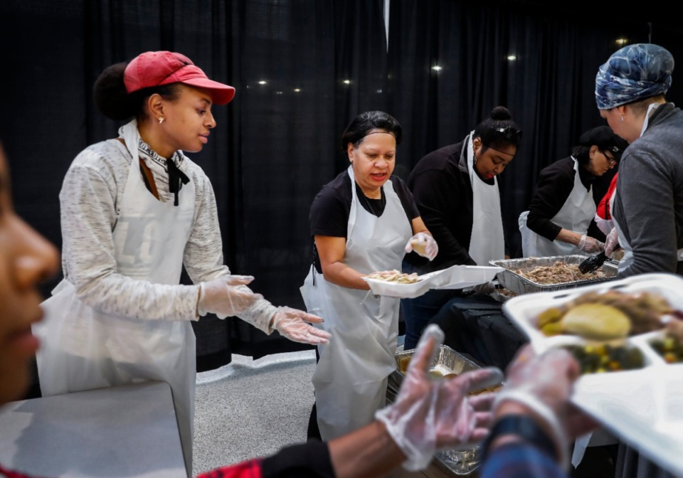 <strong>Volunteers Jamayca Harris (left) and Roslyn Jackson (middle) dish up Thanksgiving dinners during the 35th annual MemFeast, Thursday, Nov. 28, 2019 at City hall.</strong> (Mark Weber/Daily Memphian file)
