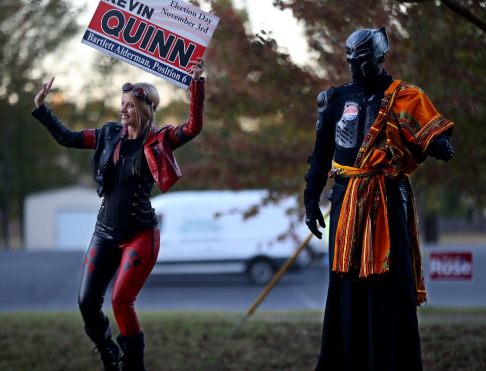 <strong>Nora Childers and Kenneth Dunn, cosplaying as Harley Quinn and Black Panther, wave signs for Bartlett alderman candidate Kevin Quinn outside Bartlett Woods Church of Christ on Tuesday, Nov. 3.</strong> (Patrick Lantrip/Daily Memphian)