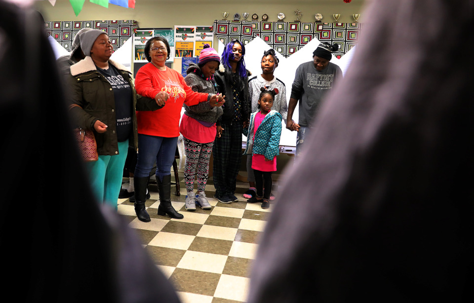 <strong>Hattie Porter, lead site director for Neighborhood Christian Centers, leads a prayer circle in NCC's Greenbriar location prior to passing out Christmas baskets to area residents on Friday, Dec. 14, 2018.</strong> (Patrick Lantrip/Daily Memphian)