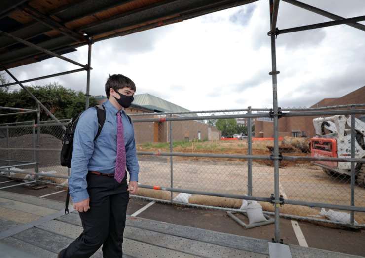 A Christian Brothers High School student (in a Sept. 3, 2020 photo) passes construction where the school's new fieldhouse is being built.(Patrick Lantrip/Daily Memphian file)