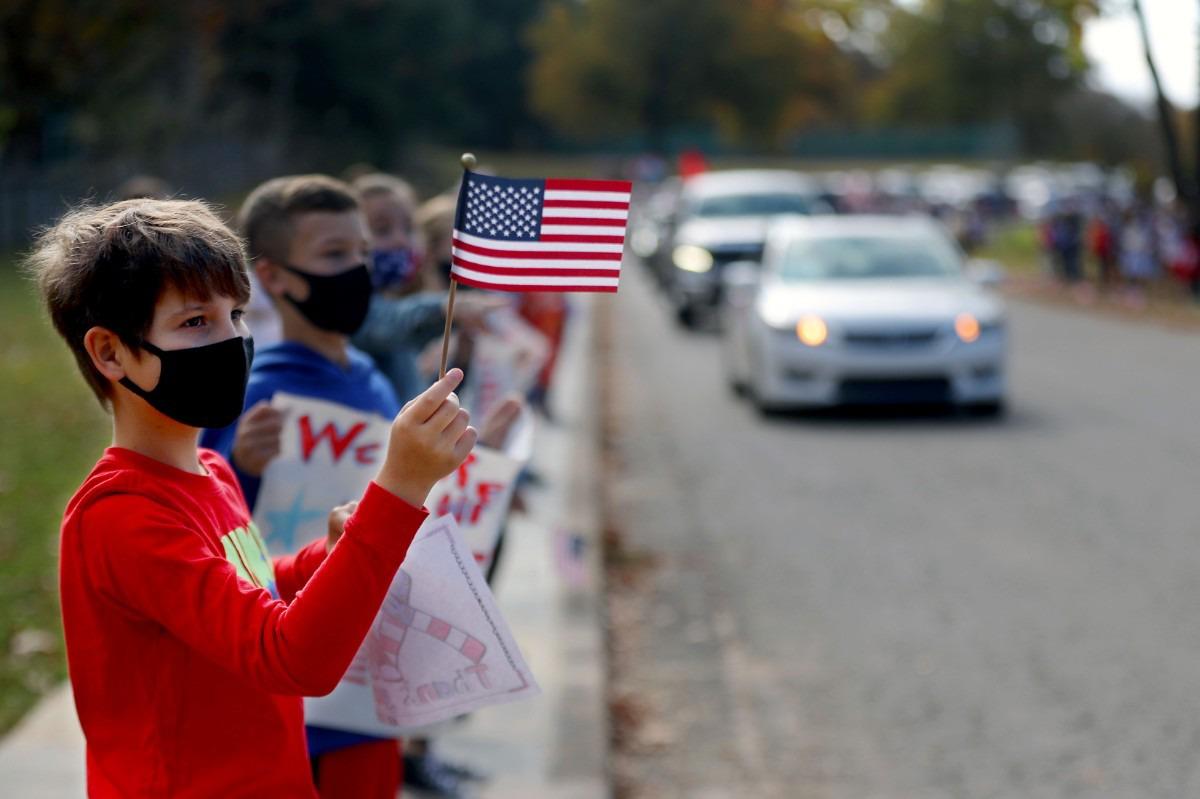 <strong>Archer Warren waves an American flag while a caravan of veterans passes by Dogwood Elementary Nov. 11, 2020.</strong> (Patrick Lantrip/Daily Memphian)