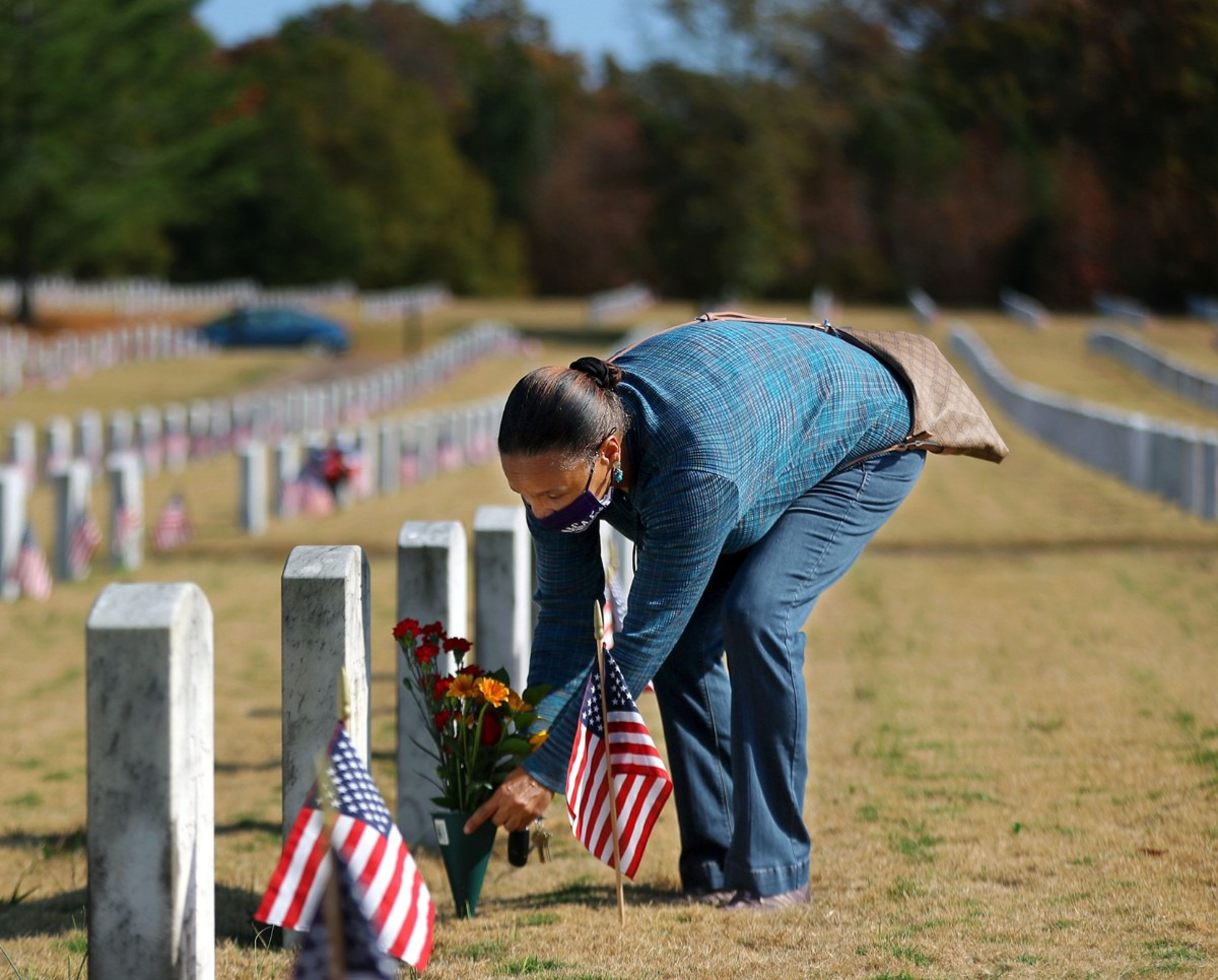 <strong>Carolyn Taylor places flowers on the grave of her brother Rodney Taylor, who was a Navy Veteran, on Veterans Day at the West Tennessee State Veterans Cemetery Nov. 11, 2020.</strong> (Patrick Lantrip/Daily Memphian)