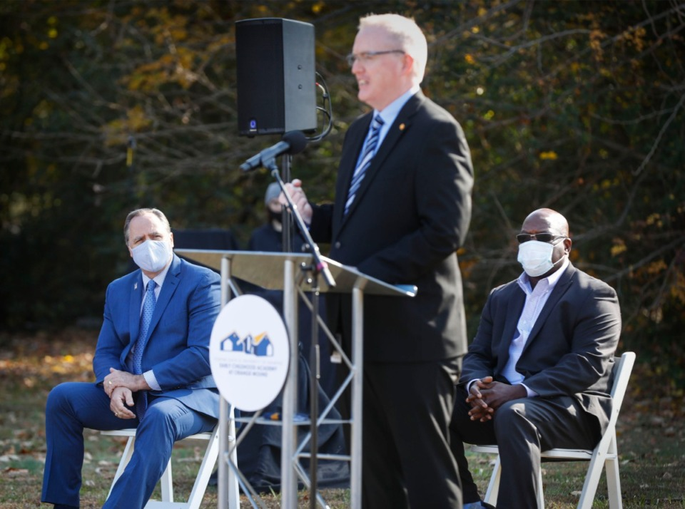 <strong>University of Memphis President David Rudd (left) and RedZone Ministries Executive Director Howard Eddings (right) listen to Porter-Leath President Sean Lee speak Wednesday at the groundbreaking.</strong> (Mark Weber/The Daily Memphian)
