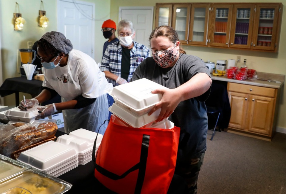 <strong>Elizabeth Scarborough packs up boxed lunches for for her eight family members at the Healthy Frayser food hub on Friday, Nov. 13, 2020 at The Neighborhood Cafe, the newest sustainability hub.</strong> (Mark Weber/The Daily Memphian)