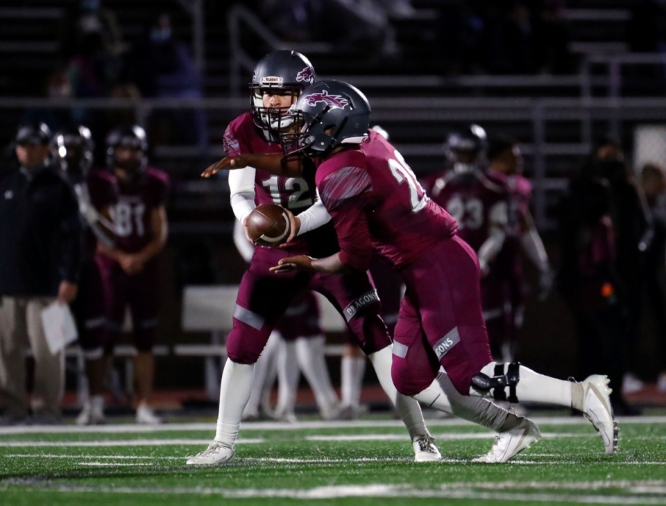 <strong>Collierville quarterback Ethan Pettigrew (12) hands the ball off to running back Troy Martin (29) during the Nov. 13, 2020, home game against Arlington.</strong> (Patrick Lantrip/Daily Memphian)