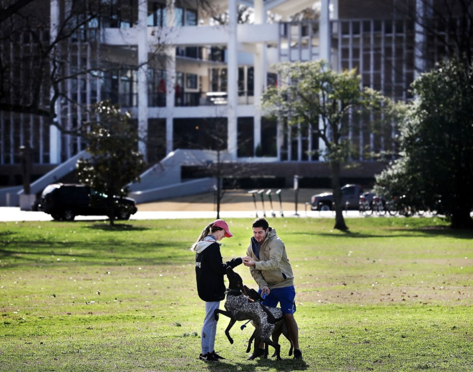 <strong>Two pedestrians play with their dogs near Rust Hall in 2019.</strong> (Jim Weber/Daily Memphian)