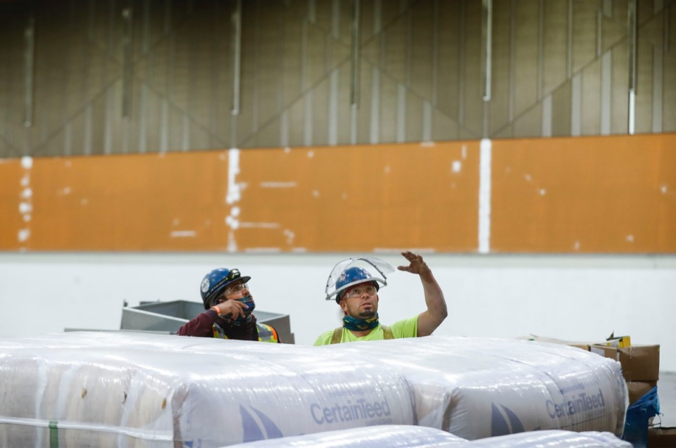 <strong>Construction workers discuss installing soundproofing materials inside the Renasant Convention Center on Nov. 17, 2020.</strong> (Mark Weber/The Daily Memphian)