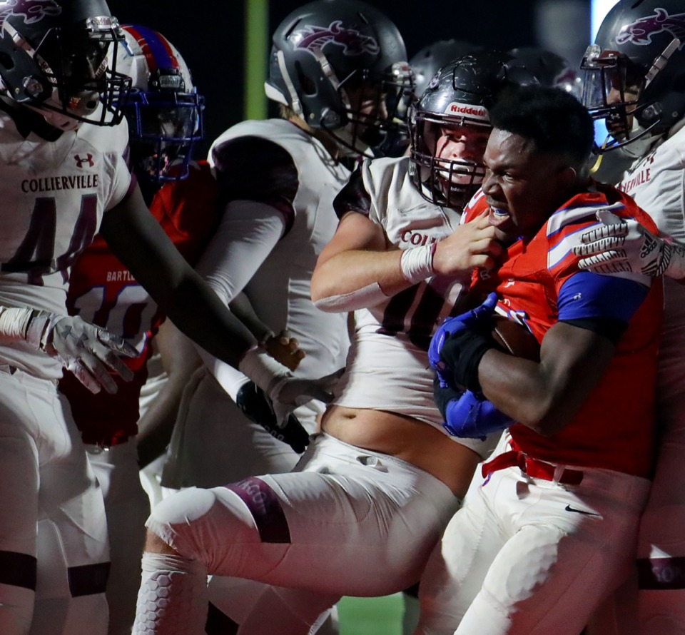 <strong>Bartlett running back Robert Giaimo (21) carries a group of Collierville defenders into the endzone with him for a touchdown, despite having his helmet ripped off.</strong> (Patrick Lantrip/Daily Memphian)