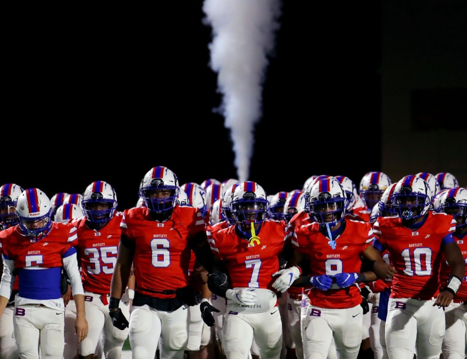 <strong>The Bartlett football team links arms as it takes the field amid a cloud of smoke before the Nov. 20, 2020, playoff game against Collierville.</strong> (Patrick Lantrip/Daily Memphian)