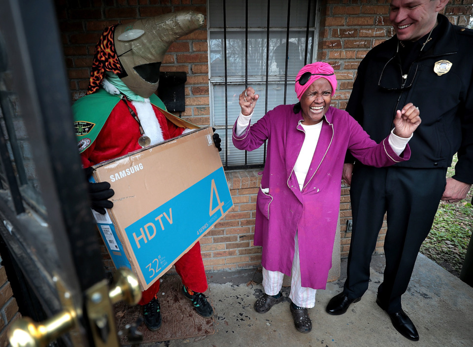 <strong>Burglary victim Sylvia Crump cheers for her new TV as she thanks the Memphis Police Department officers and Boll Weevils who showed up on her doorstep on Wednesday, Dec. 19, to replace Christmas gifts that were stolen from her house. MPD and the Weevils partnered with Target to make surprise deliveries to more than a dozen households that were recently burglarized.</strong> (Jim Weber/Daily Memphian)