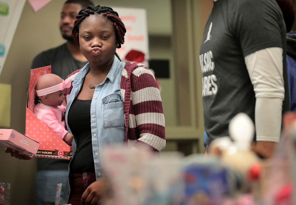 <strong>Tatyana Bellamy tries to make a tough toy choice while shopping for her 2-year-old during the Neighborhood Christian Center's annual Christmas toy store on Thursday, Dec. 20. The event provides more than 500 families with the opportunity to choose gifts for their children.</strong> (Jim Weber/Daily Memphian)