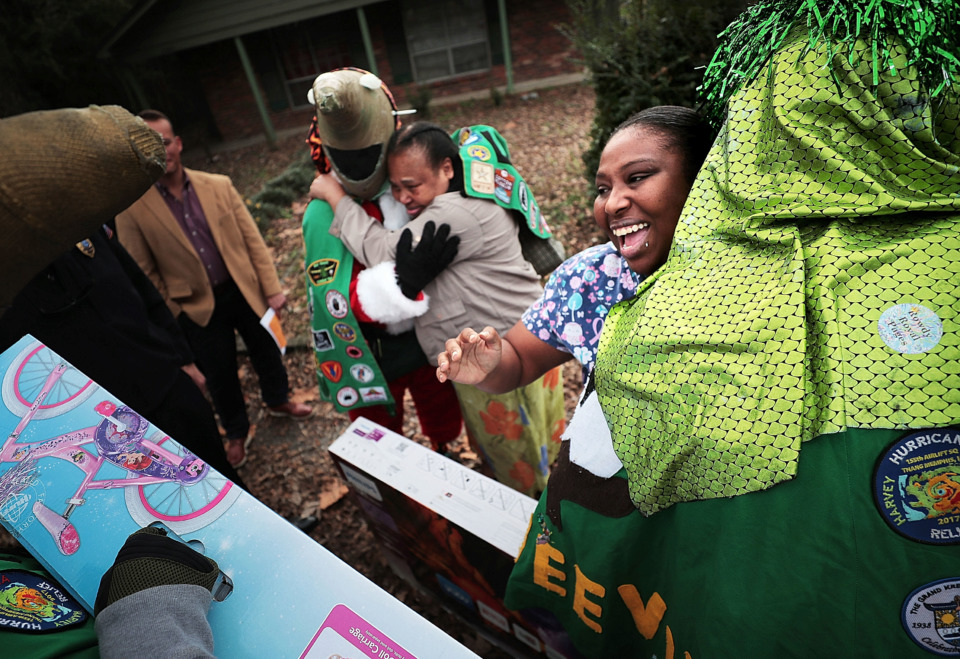 <strong>Burglary victim Monica Lawrence (right) and her mother, Shirley McGhee, thank Memphis Police officers and Boll Weevils who delivered items on Wednesday, Dec. 19, to replace Christmas gifts that were stolen from their home.</strong> (Jim Weber/Daily Memphian)