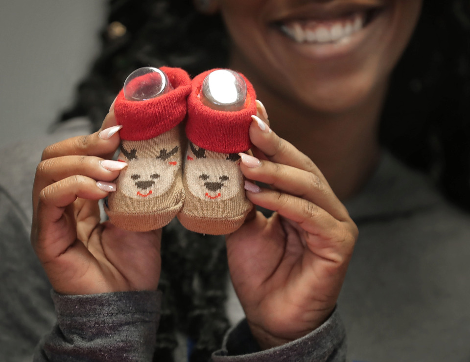 <strong>Sandi Sadler with the Office of Youth Services shows off a pair of baby booties as youths with the Memphis Ambassadors Program sort through winter wear collected during their charity coat drive. MAP collected more than 1,200 clothing items to distribute to needy kids at Memphis community centers, Meritan foster care and area schools.</strong> (Jim Weber/Daily Memphian)
