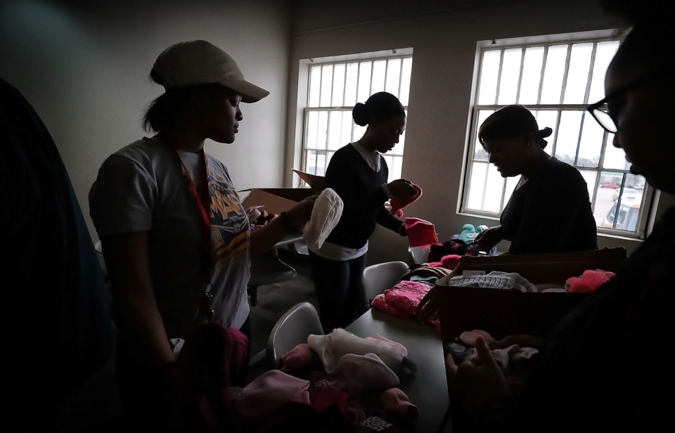 <strong>Youths with the Memphis Ambassadors Program and their parents sort through winter wear on Dec. 19, 2018 that was collected during MAP's charity coat drive. MAP kids collected more than 1,200 clothing items to distribute to needy children at Memphis community centers, Meritan foster care and area schools.</strong> (Jim Weber/Daily Memphian)