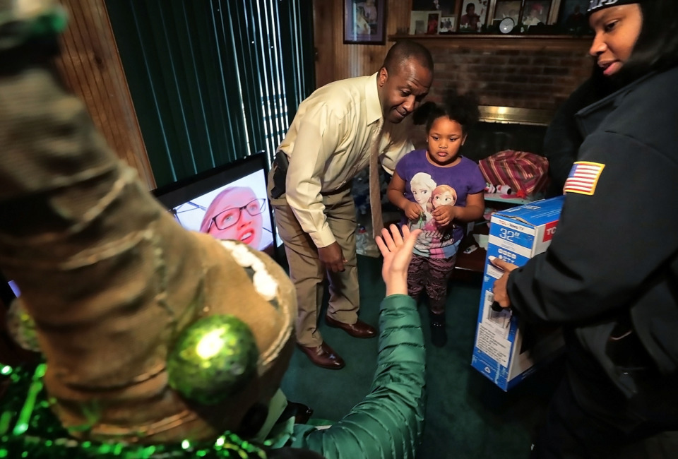 <strong>Burglary victim Terri Hanna Nixon, 5, shies away from one of the strangely dressed Boll Weevils who delivered gifts to her family on Wednesday, Dec. 19. MPD officers and the Weevils surprised more than a dozen households that were burglarized recently.</strong> (Jim Weber/Daily Memphian)
