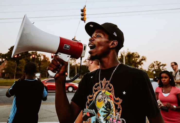 <strong>Mario Denton, 26, shouts through a speaker during a protest on Wednesday, Sept. 19, in front of the Airways police precinct. Demonstrators gathered in front of the precinct to protest the actions of two police officers who turned off their body cameras prior to the shooting of an African-American man on Sept. 17.</strong> (Houston Cofield/Daily Memphian)