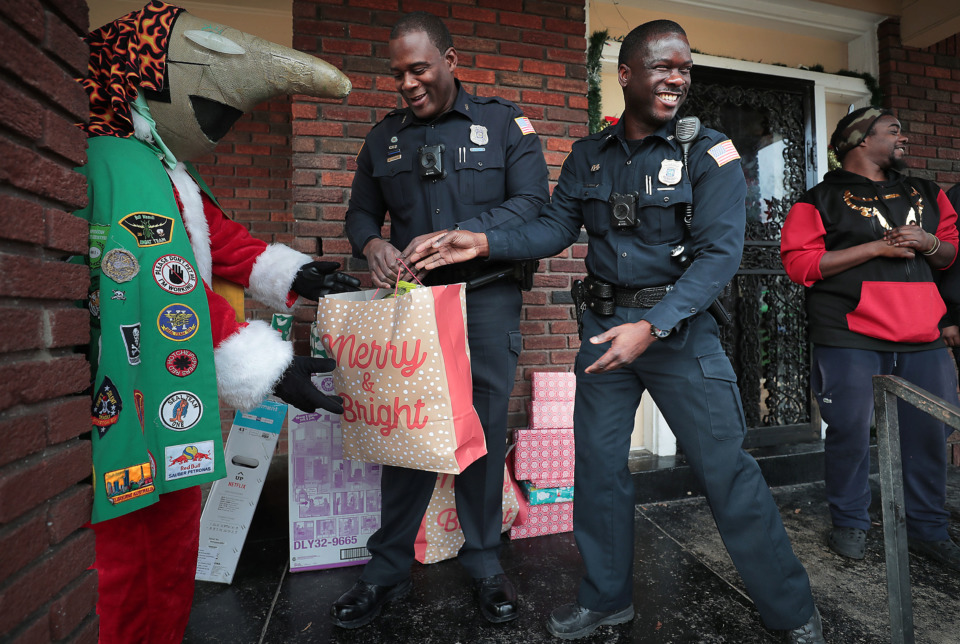 <strong>Memphis Police officers unload gifts at burglary victim Stacie Jackson's South Memphis home on Wednesday, Dec. 19.</strong> (Jim Weber/Daily Memphian)