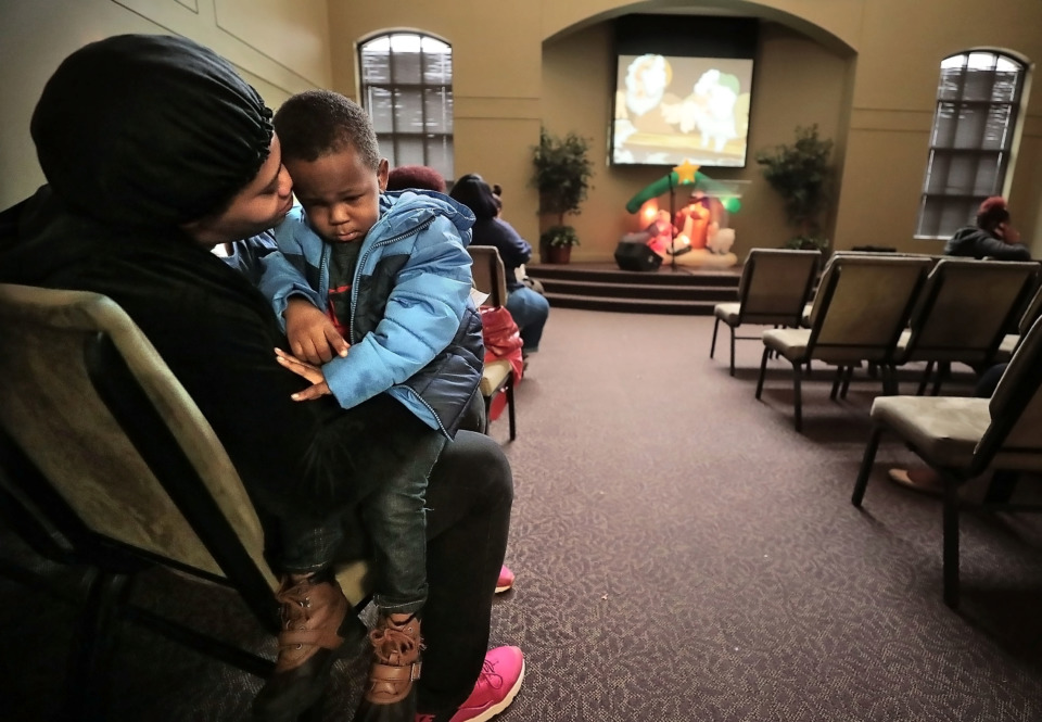 <strong>Jameshua Clark and her son Logan Williams, 2, wait to shop for stocking-stuffers during the Neighborhood Christian Center's annual Christmas toy store on Thursday, Dec. 20.</strong> (Jim Weber/Daily Memphian)