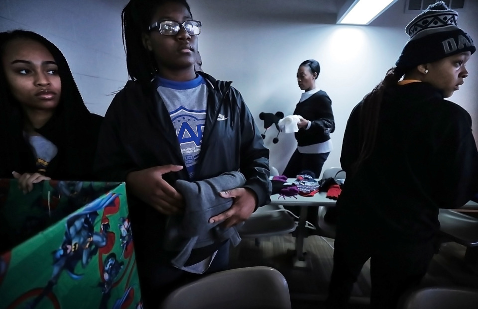 <strong>Sheniqua Woodard (from left), Christina Elliott and Briauna Stewart sort through winter clothing items collected during the coat drive held by the Memphis Ambassadors Program. MAP collected more than 1,200 clothing items to distribute to needy kids.</strong> (Jim Weber/Daily Memphian)