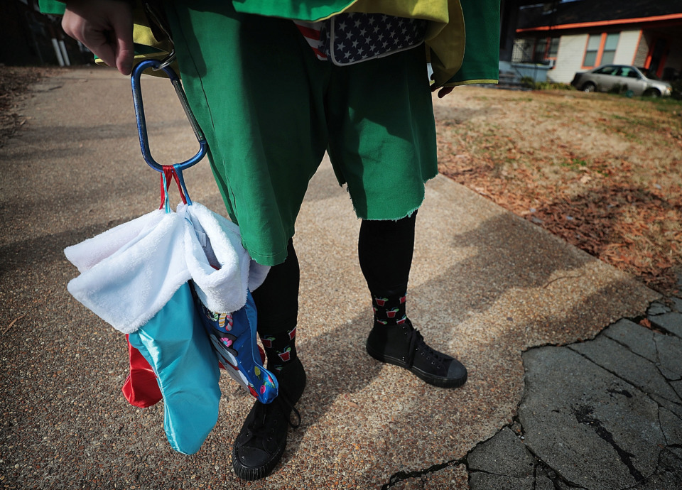 <strong>One of the Memphis Boll Weevils delivers Christmas presents to victims of recent burglaries.</strong> (Jim Weber/Daily Memphian)