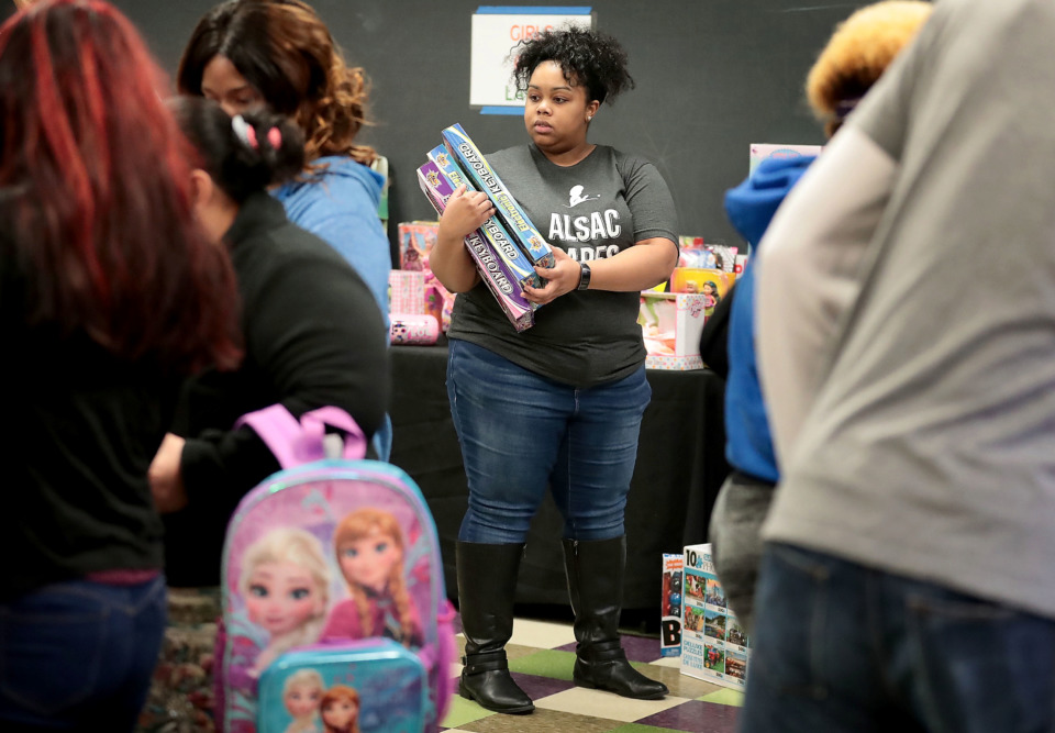 <strong>Volunteer Jarmeese Morrow helps shoppers during the Neighborhood Christian Center's annual Christmas toy store on Thursday, Dec. 20. The NCC provided more than 500 families with the opportunity to choose presents for their children.</strong> (Jim Weber/Daily Memphian)