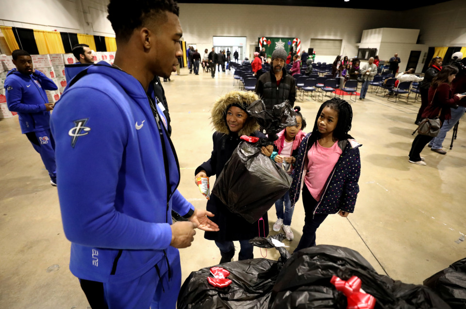 <strong>Antwann Jones (left), a guard for the University of Memphis basketball team, hands a bag of Christmas gifts to Jordan Brunson (center) during a toy drive hosted by the University of Memphis and the City of Memphis.</strong> (Houston Cofield/Daily Memphian)