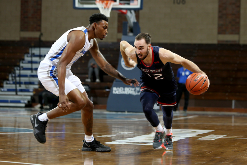<strong>Tommy Kuhse (12) of the Saint Mary's Gaels looks to drive past D.J. Jeffries (0) of the Memphis Tigers during the Bad Boy Mowers Crossover Classic at the Sanford Pentagon in Sioux Falls, SD.</strong> (Photo by Dave Eggen/Inertia)