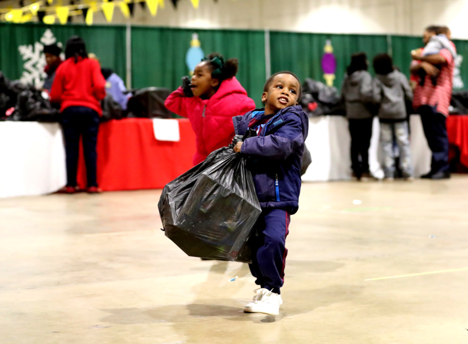 "<strong>Zion Banks, 3, lifts a heavy bag of toys he picked up from the ""Tiger Toy Drive"" hosted by the University of Memphis men's basketball team and the City of Memphis.</strong> (Houston Cofield/Daily Memphian)"
