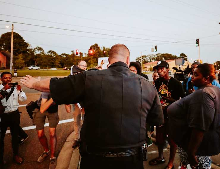<strong>A Memphis police officer directs protesters to a different sidewalk along Airways Boulevard. Demonstrators gathered in front of the precinct to protest the actions of two police officers who turned off their body cameras prior to the shooting of an African-American man on Sept. 17.</strong> (Houston Cofield/Daily Memphian)