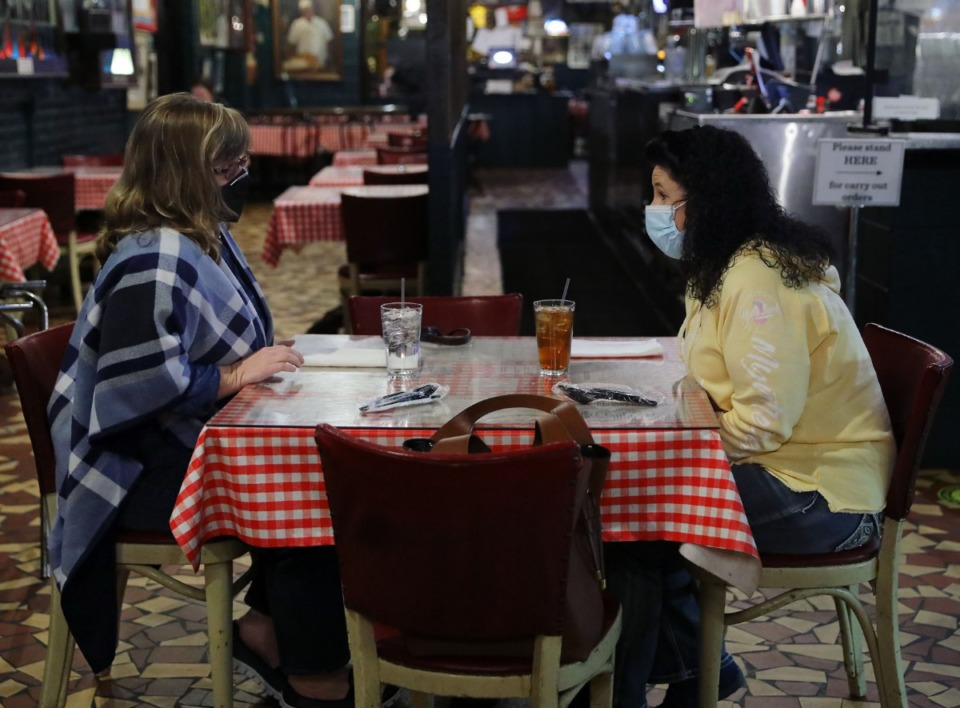 <strong>Denise Tate (left) and Ramona Snow chat with masks on, while waiting on their food during lunch at Rendezvous Dec. 1, 2020.</strong> (Patrick Lantrip/Daily Memphian)