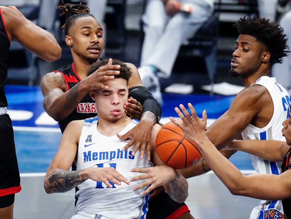 <strong>Memphis guard Lester Quinones (bottom) battles Arkansas State defender Markise Davis (top) for a rebound as teammate Ahmad Rand (right) helps on the play.</strong> (Mark Weber/The Daily Memphian)