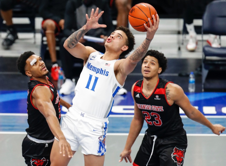 <strong>Tiger guard Lester Quinones (middle) makes a layup against Arkansas State&rsquo;s Christian Willis (left) and Marquis Eaton (right).</strong> (Mark Weber/The Daily Memphian)