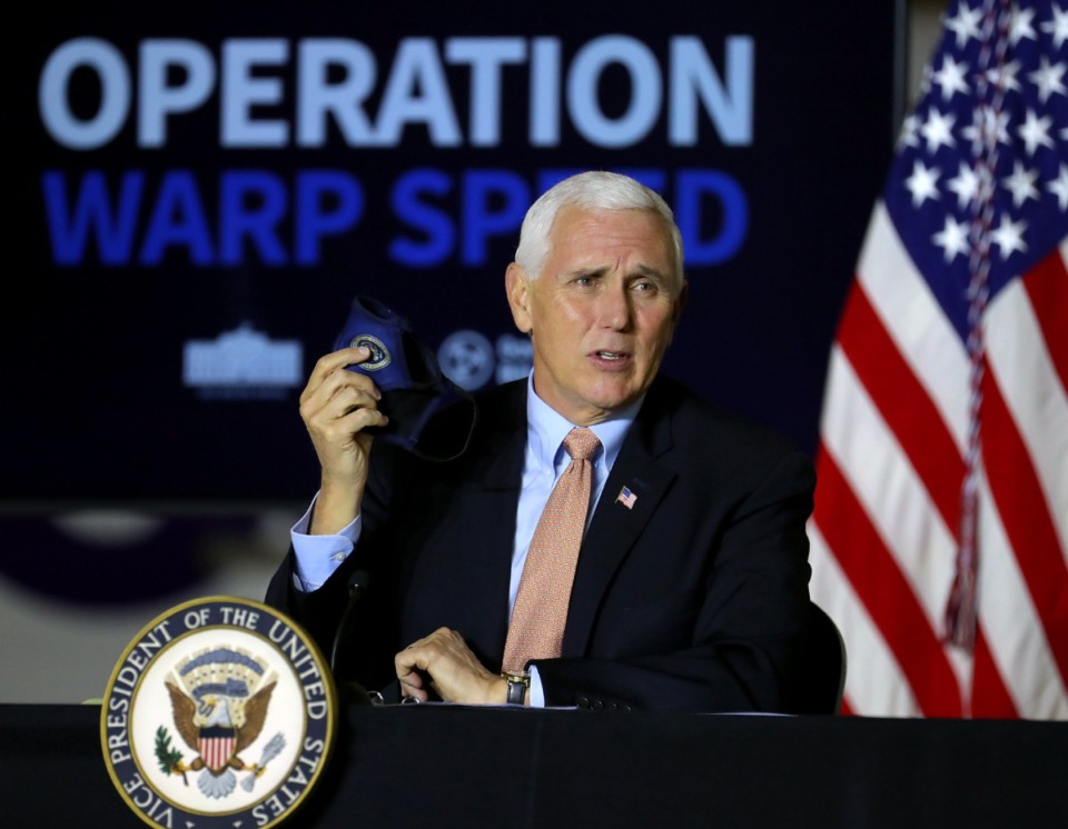<strong>Vice President Mike Pence holds up a mask while giving an update on Operation Warp Speed in an Air National Guard hanger in Memphis, Dec. 3, 2020.</strong> (Patrick Lantrip/Daily Memphian)