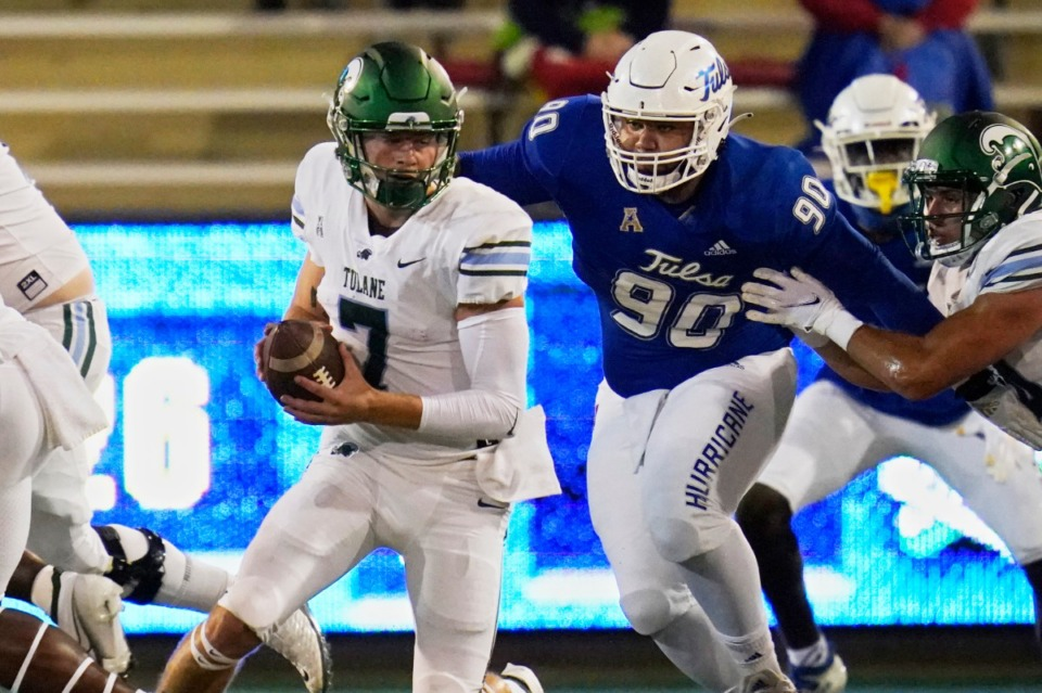 <strong>Tulane quarterback Michael Pratt (7) is pursued by Tulsa defensive lineman Jaxon Player (90) on Nov. 19. This game is the only one of the last four that the Green Wave has lost, and it was in double overtime in Tulsa, which is ranked No. 24.</strong> (Sue Ogrocki/AP file)