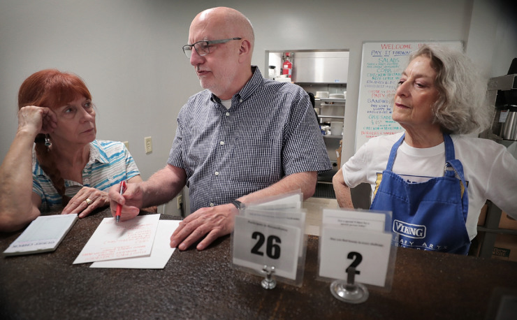 <strong>Mac Edwards talks with volunteers Eddie Thomas (right) and Trish McGhee about the menu before the lunch rush at Caritas Village, which reopened on August 29, 2018. Edwards closed Pharm2Fork in Collierville early in the year, but went on to become the executive director of Caritas Village.</strong> (Jim Weber/Daily Memphian file)