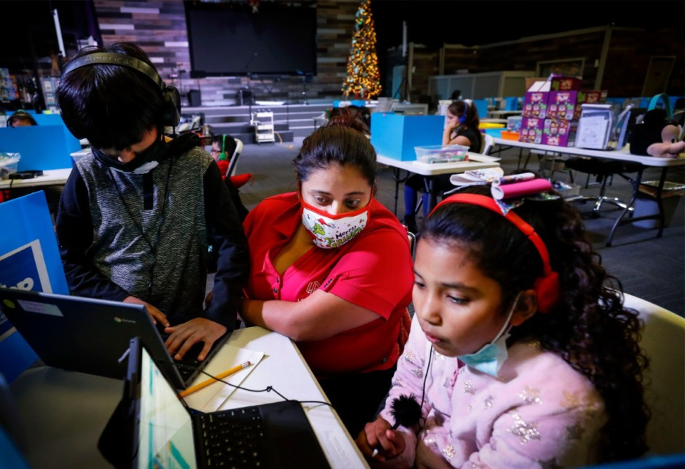 <strong>Education specialist Adriana Cortes (middle) works with fourth grade students Stephen Escalante (left) and Zoe Centeno (right) while they attend virtual school at Las Americas on Monday, Dec. 7, 2020.</strong> (Mark Weber/The Daily Memphian)