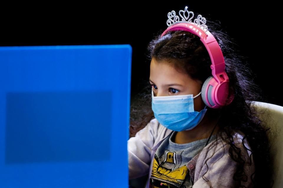 <strong>Third grader Maria Daniela Ortega wears a mask and royalty headphones while attending virtual school inside socially distance desks at Las Americas on Monday, Dec. 7, 2020.</strong> (Mark Weber/The Daily Memphian)