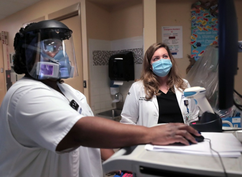 <strong>Trishonda Scurlock (left) and Dr. Amber Thacker (in a file photo) go over patient data in a Regional One COVID ward. Hospitalizations and COVID-related deaths are up in Shelby County.</strong> (Patrick Lantrip/Daily Memphian)
