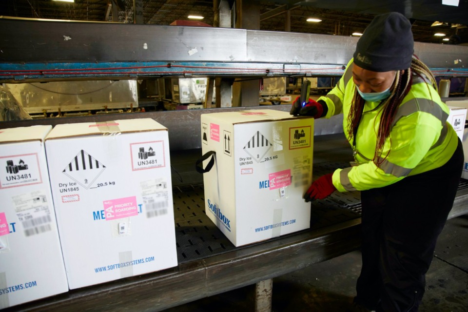 <strong>A package handler at the FedEx Express world hub in Memphis adjusts a box of Pfizer/BioNTech&rsquo;s COVID-19 vaccine during sorting on Sunday, Dec. 13.</strong> (Courtesy FedEx)