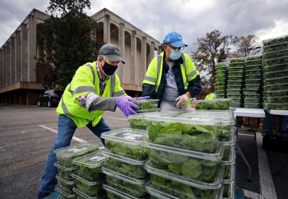 <strong>Pat Warren (left) stacks up hundreds of boxes of spinach to be given out to needy families at Lindenwood Christian Church Nov. 14, 2020.</strong> (Patrick Lantrip/Daily Memphian)
