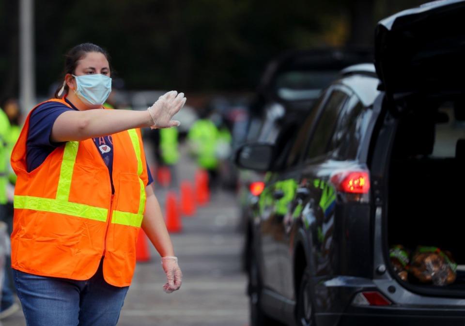 <strong>Alana Wells directs traffic as hundreds of cars line up to pick up food donations at Lindenwood Christian Church Nov. 14, 2020.</strong> (Patrick Lantrip/Daily Memphian)