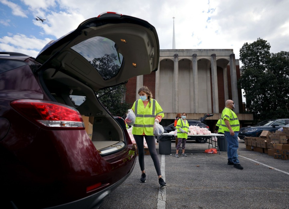 <strong>Rachel Schwam loads up a family's trunk with donated food at Lindenwood Christian Church Nov. 14, 2020.</strong> (Patrick Lantrip/Daily Memphian)