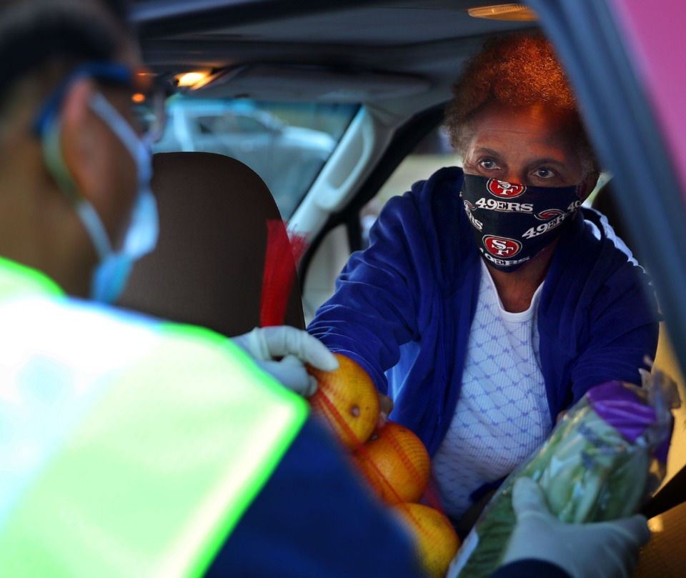 <strong>Beulah Moss-Thomas picks up fresh food from a volunteer during a monthly food giveaway at Lindenwood Christian Church Dec. 12, 2020.</strong> (Patrick Lantrip/Daily Memphian)