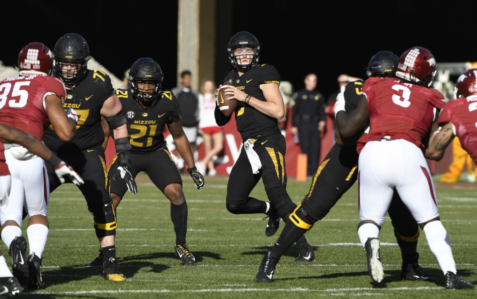 "<p class=""regdt""><strong>Missouri quarterback Drew Lock drops back to pass against Arkansas during the first half of a Nov. 24, 2018, game in Fayetteville, Ark.</strong> (AP Photo/Michael Woods)"
