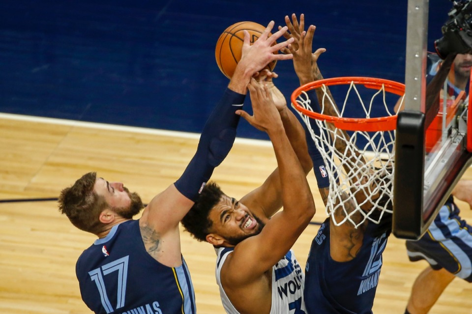 <strong>Minnesota Timberwolves center Karl-Anthony Towns (32) drives to the basket between Memphis Grizzlies center Jonas Valanciunas (17) and guard Ja Morant (12) in the first quarter of a preseason NBA basketball game Monday, Dec. 14, 2020, in Minneapolis.</strong> (Bruce Kluckhohn/AP)